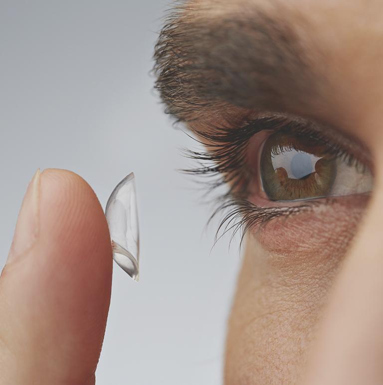 mężczyzna wkładający soczewkę do oka